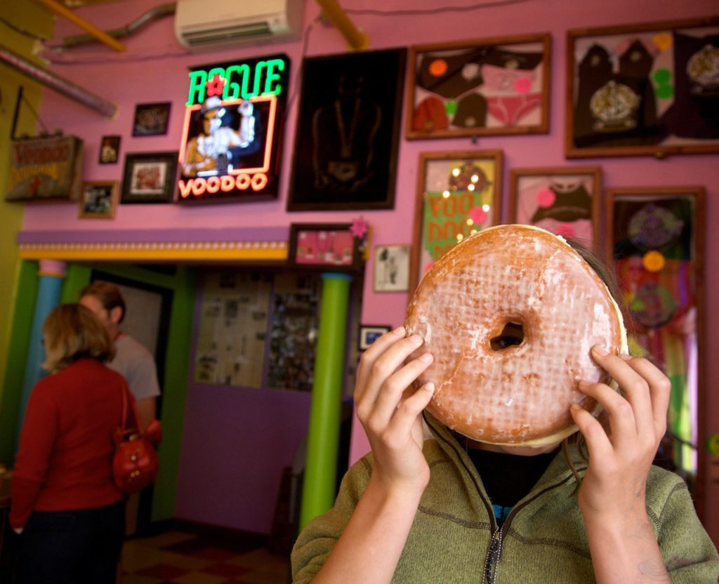 A person holds a head-sized doughnut in front of their face