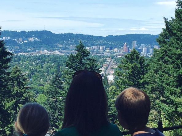 A woman and two children enjoy the view of of Portland from the top of Mt. Tabor park.