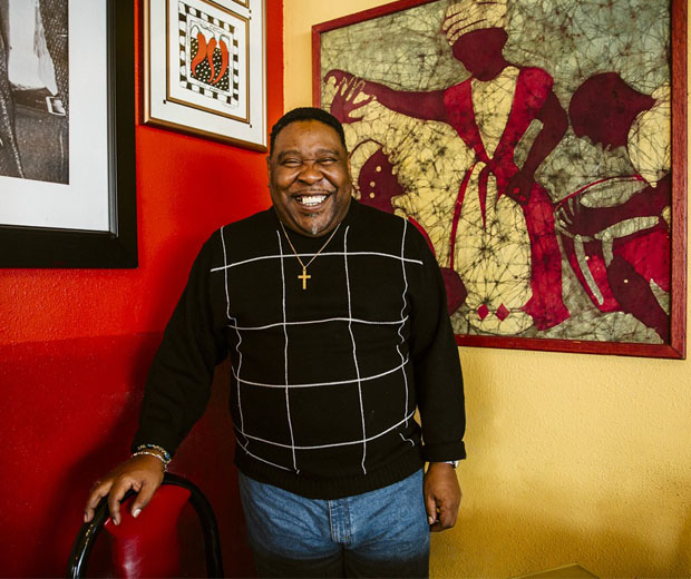 Man smiling in front of art hanging on walls of Po'Shines restaurant