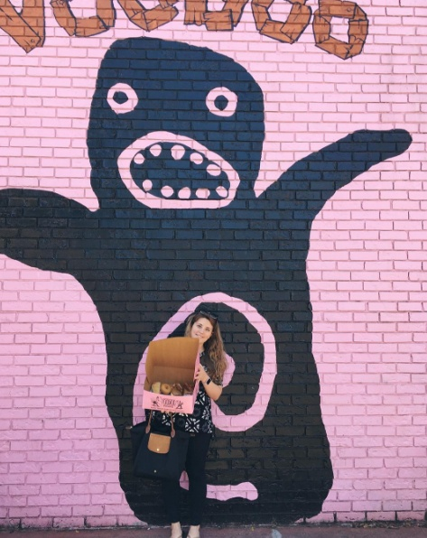 A woman stands in front of  Voodoo Doughnuts holding an open box of dougnuts