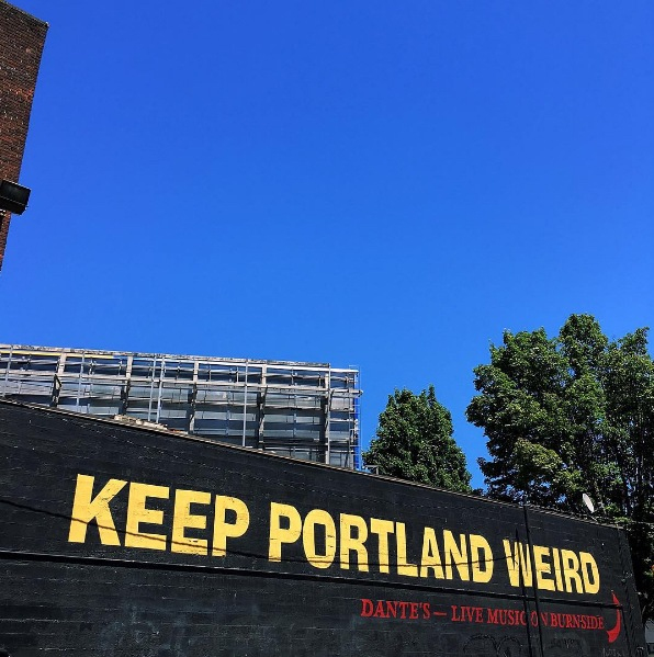 """The words """"Keep Portland Weird"""" painted in yellow on the side of a black building."""