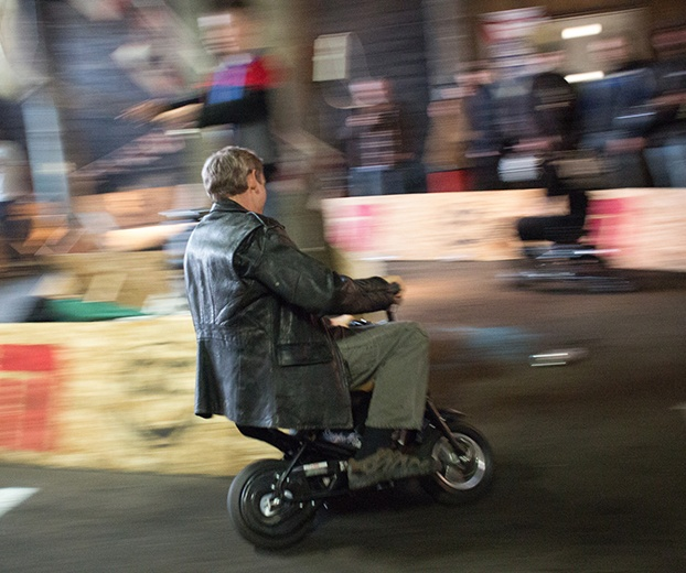 An adult wearing a leather jacket rides a mini bike
