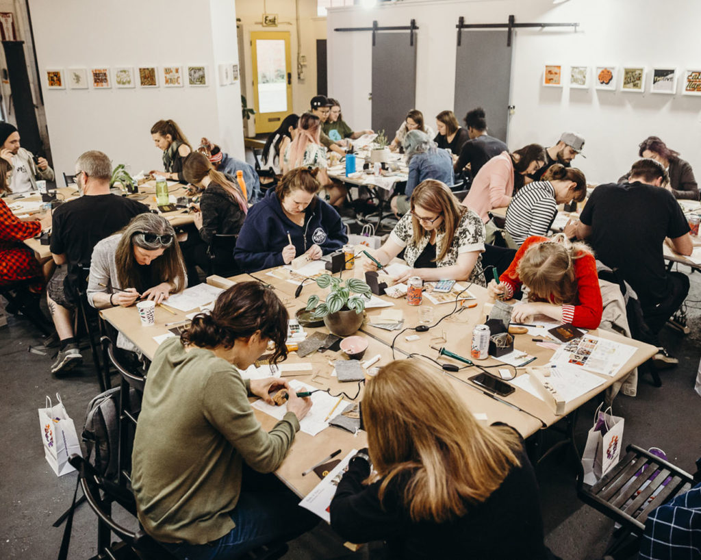 dozens of people gathered around large tables making art in a cannabis safe space