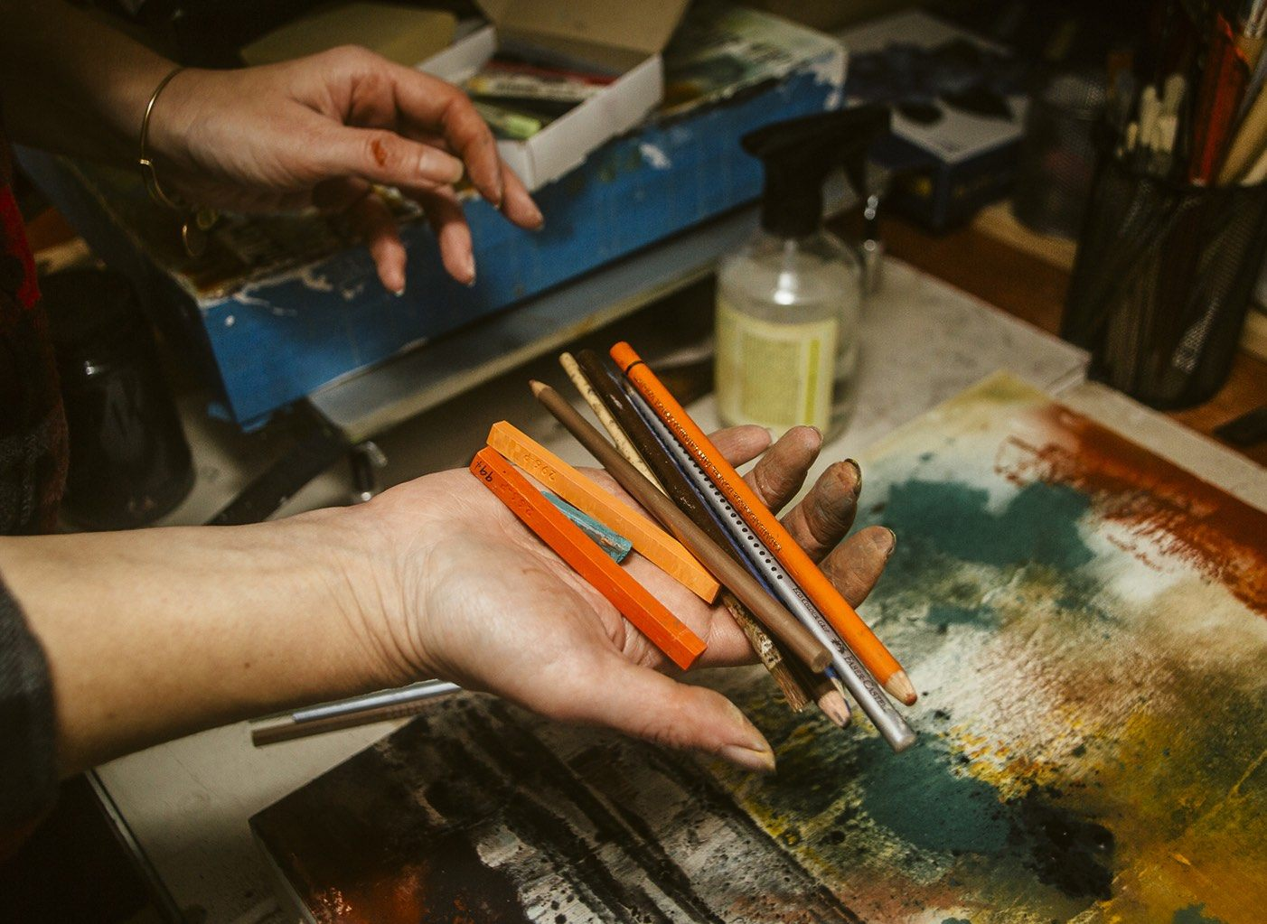 an artist holding pencils, crayons and other art-making implements