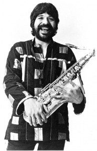 A smiling man holding a saxaphone