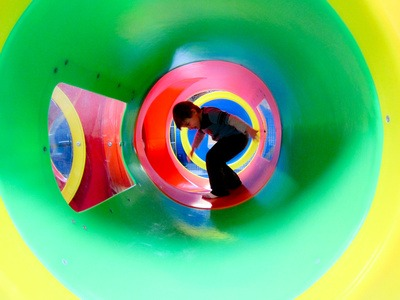 a child plays inside a green tube