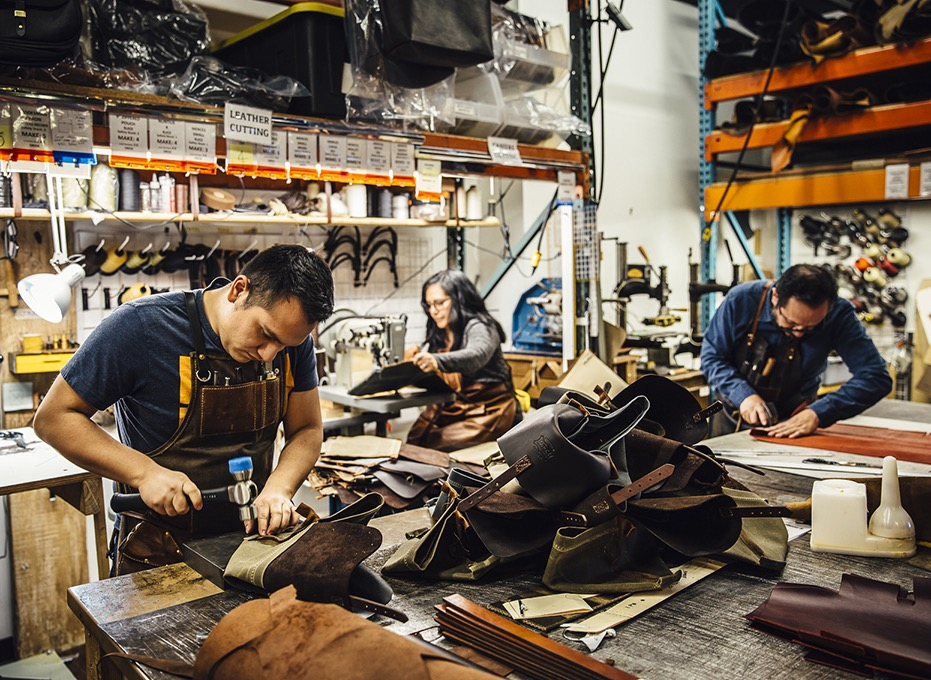 people working on leather hand-made items at workbenches