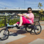 A woman pedals a recumbent three-wheeled bike with a bridge in the background