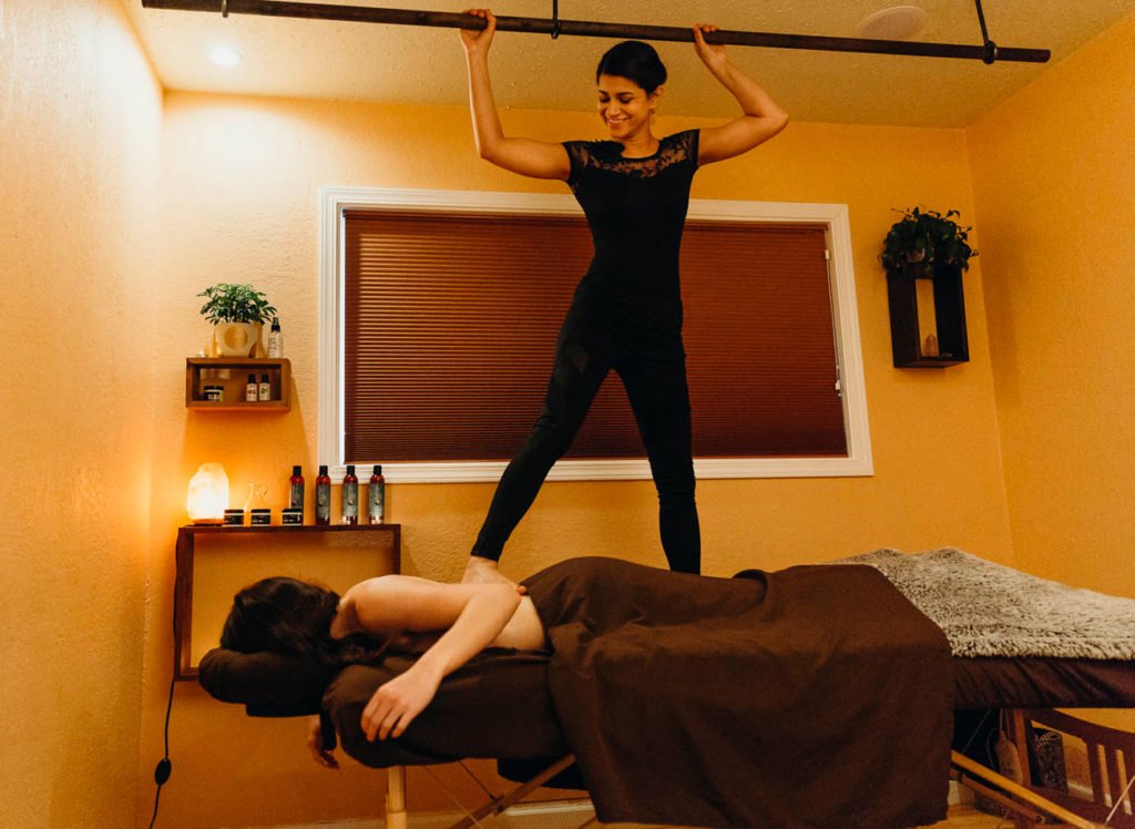 massage therapist standing on client's back at Blue Marigold