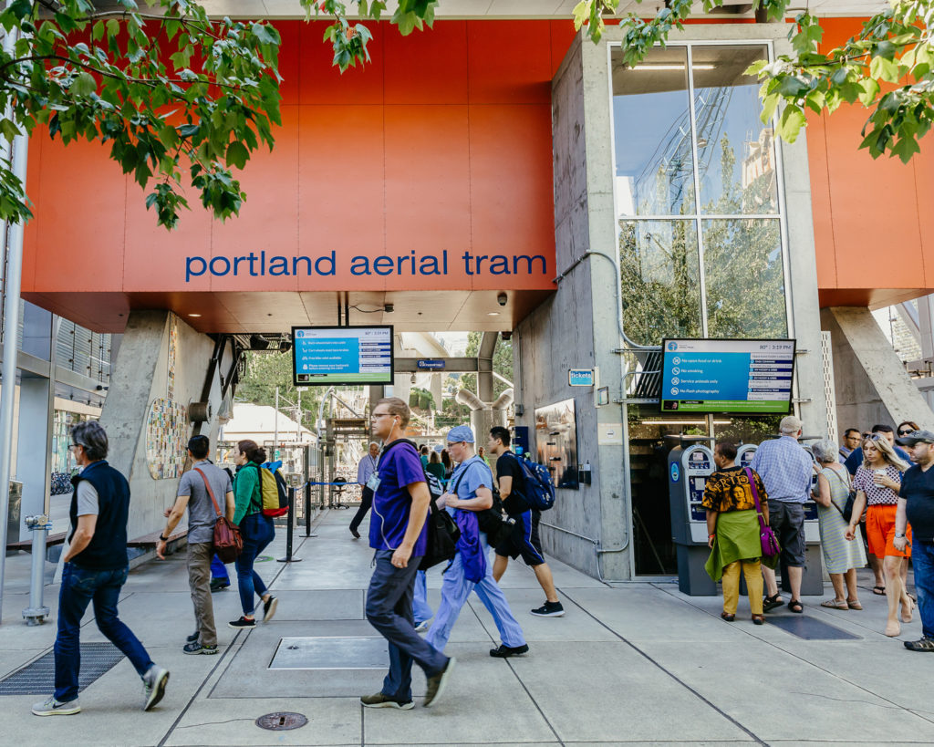 People walk by a transit station for the  aerial tram