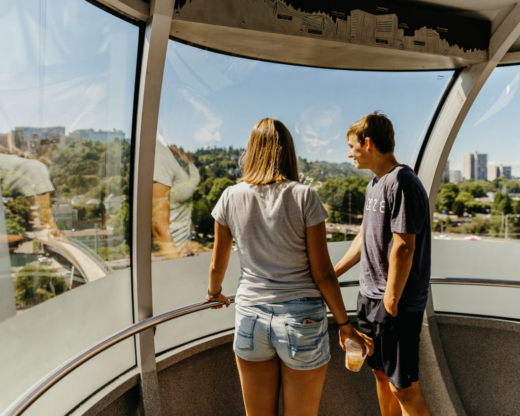Two people stand inside a rounded aerial tram cabin, observing the forest and buildings below