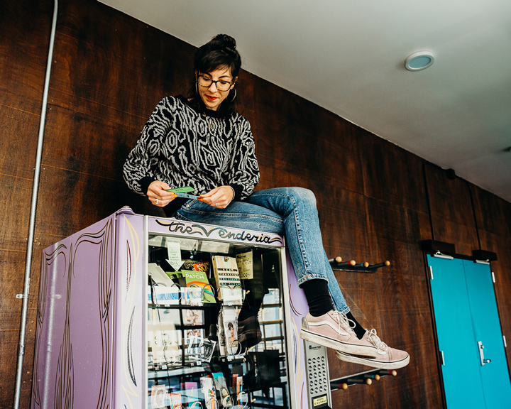 person sitting on top of a vending machine