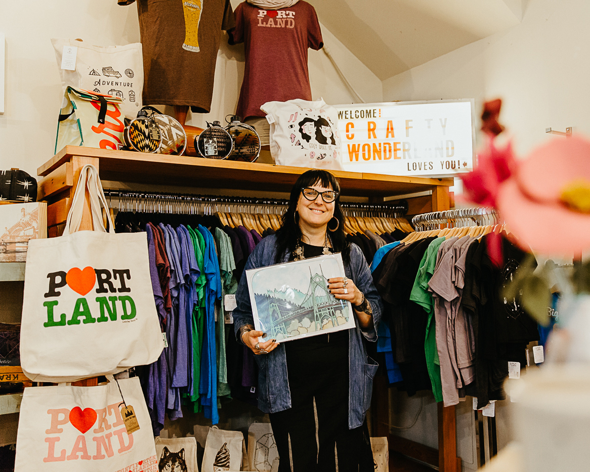 """Co-founder Cathy Zwicker holds up a print of a Portland bridge, surrounded by tote bags that say """"Portland"""" and other Portland-related merch."""