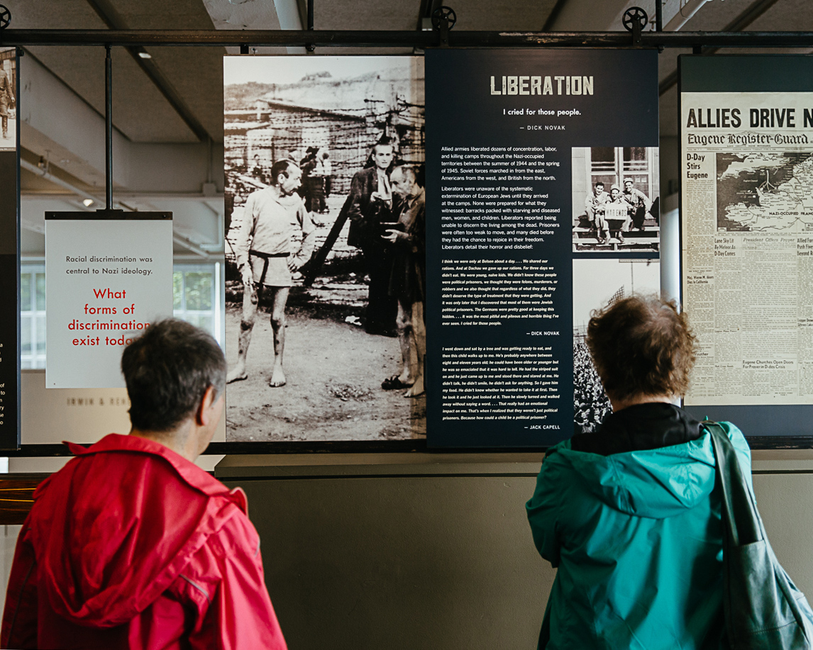 two people read an informational placard at the holocaust museum