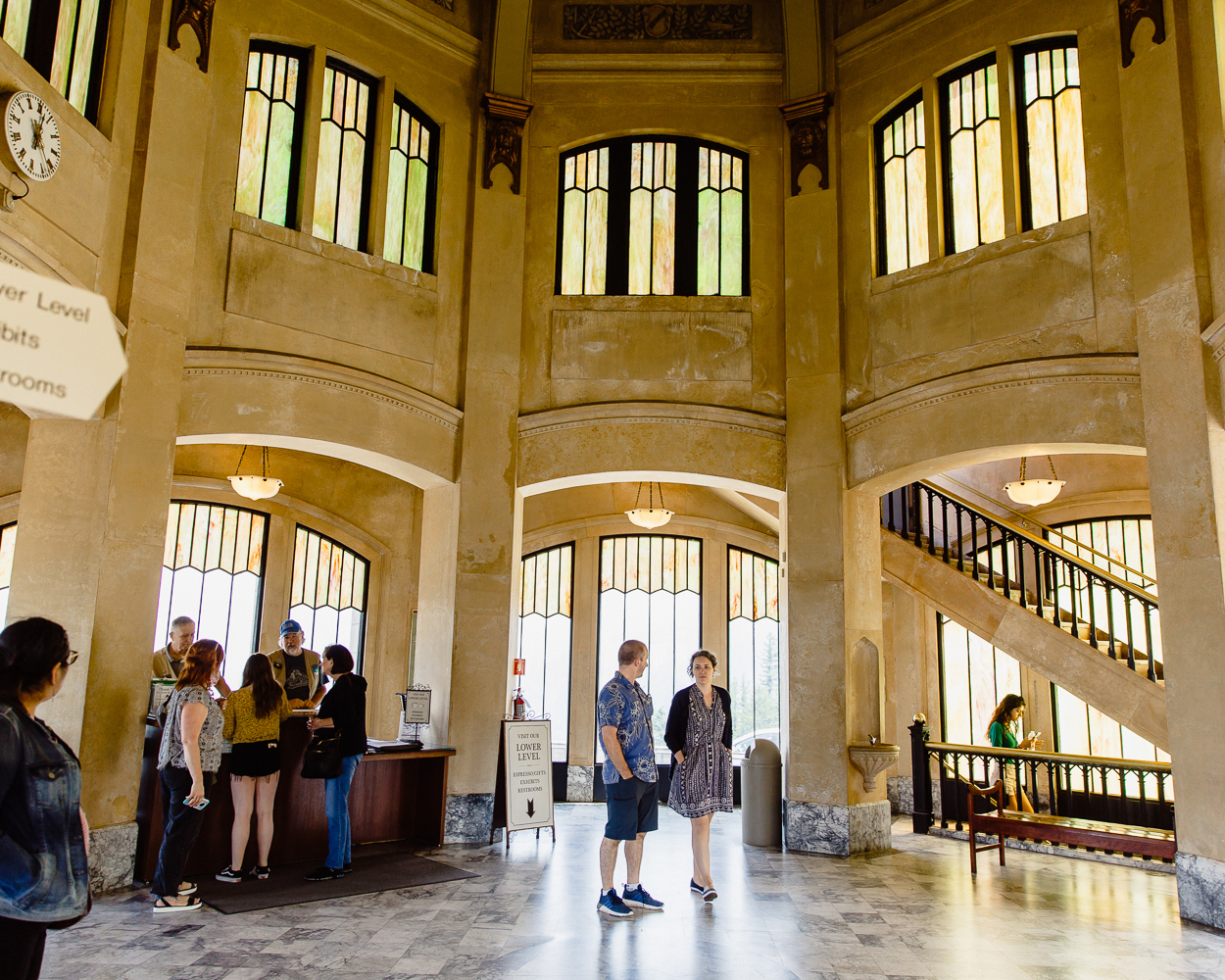 the interior entrance of the vista house, featuring tall ceilings and visitors milling about