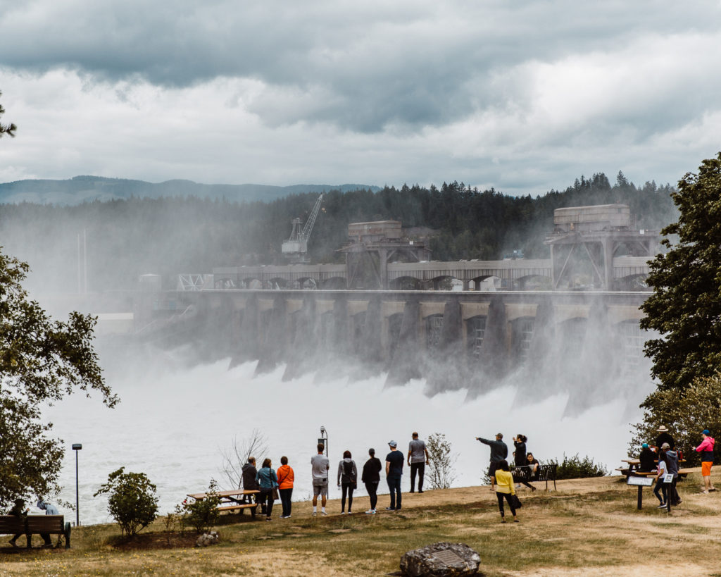 People stand on a river bank observing water flowing over a large dam