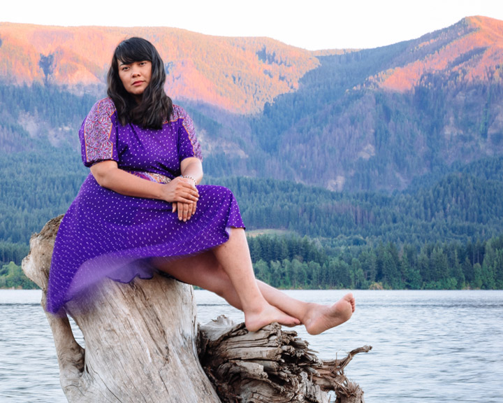 Katherine Paul sits on tree stump in front of mountain and lake vista