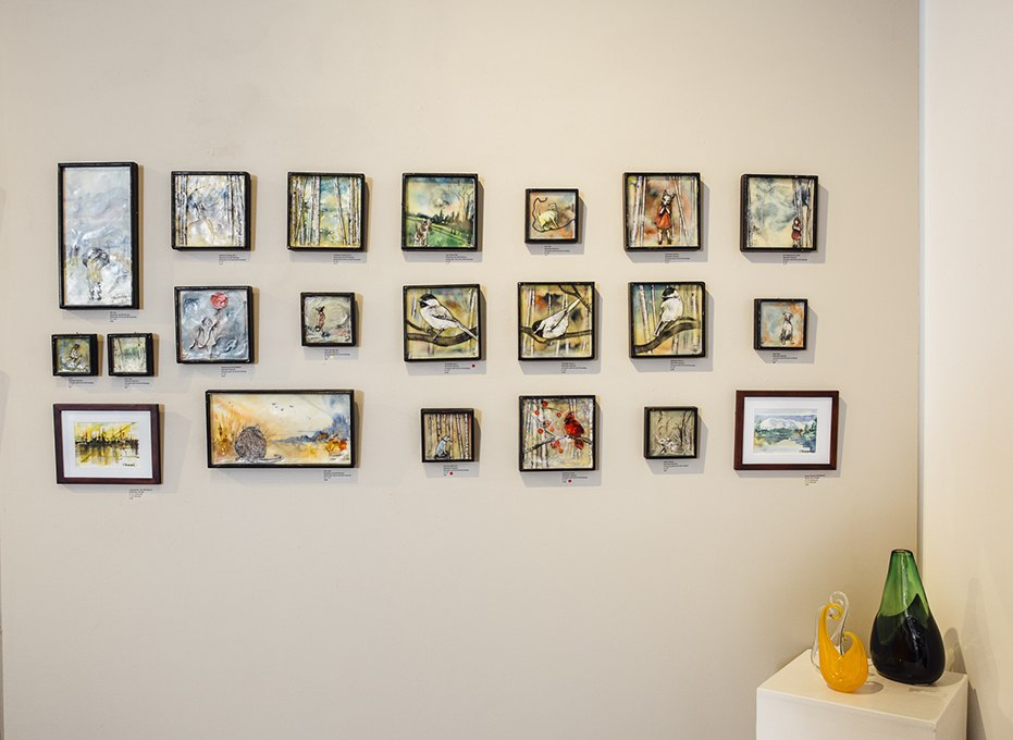 Collection of small framed art hanging on wall of J. Pepin Art Gallery