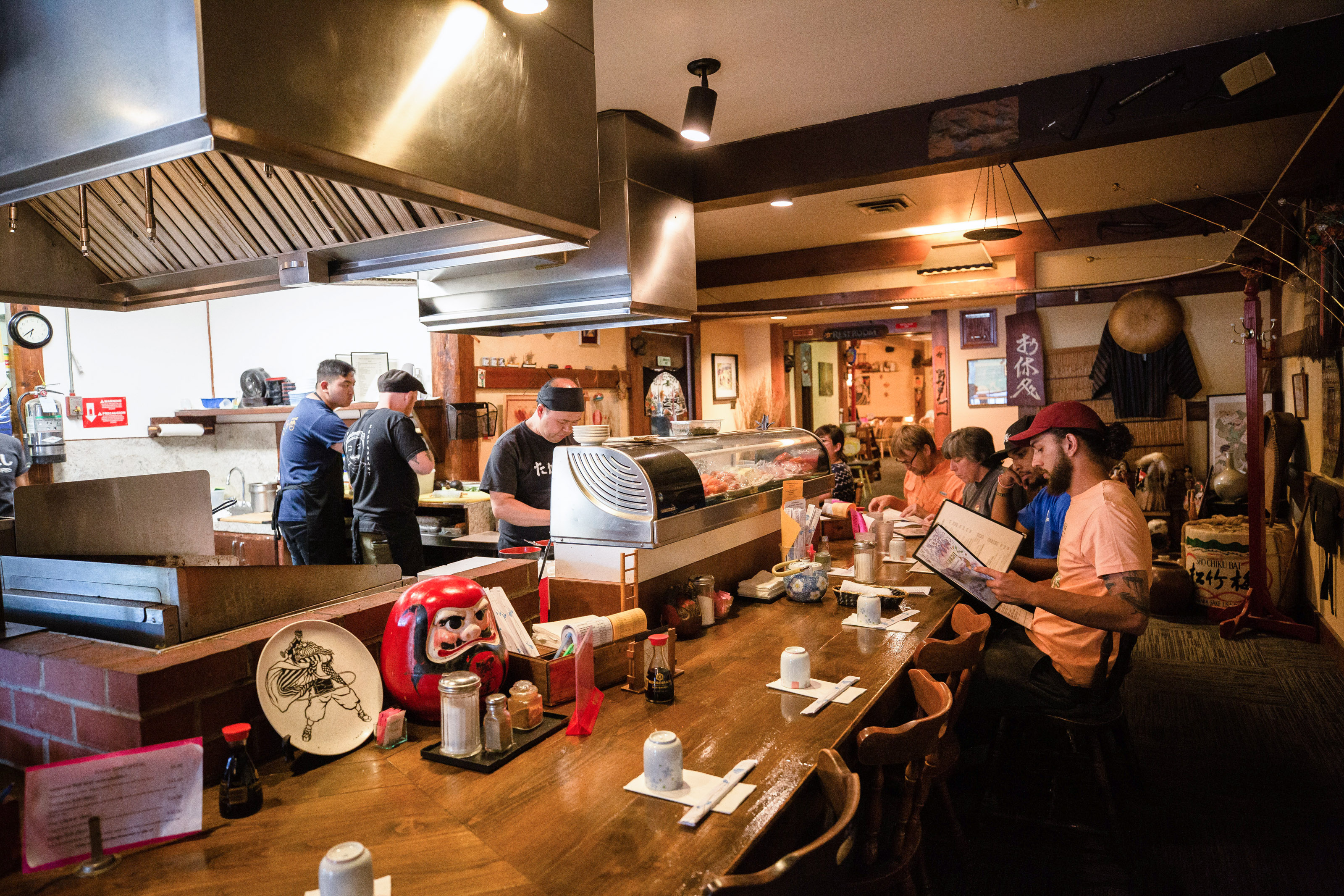 Customers sit around a bar while sushi chefs work