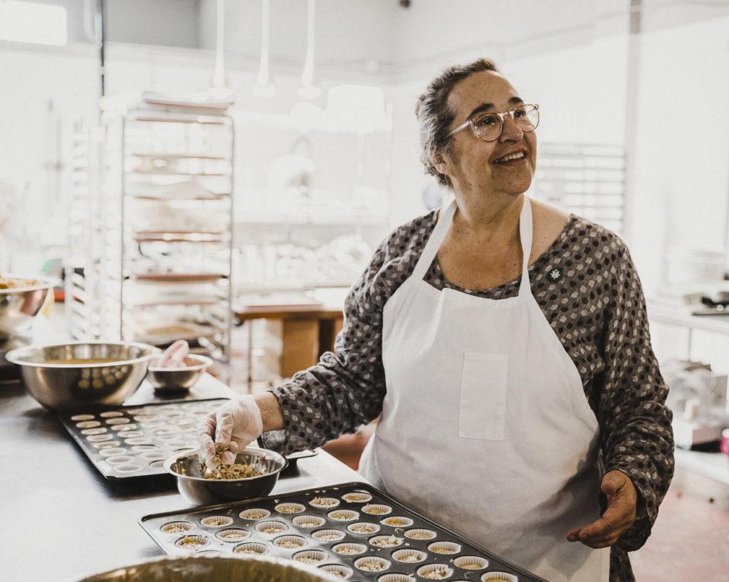 Woman preparing a muffin tin full of edible cannabis muffins.