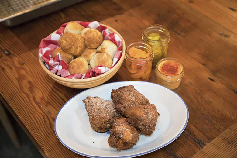 a table set with biscuits, fried chicken and beverages