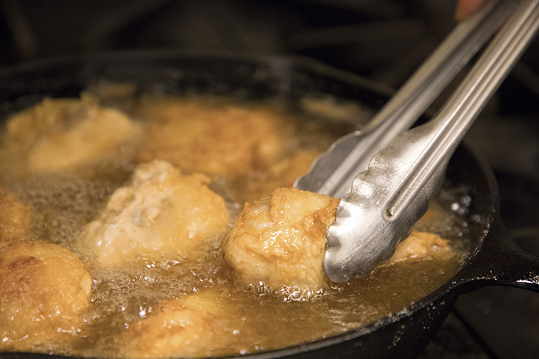 chicken being fried in a cast iron skillet