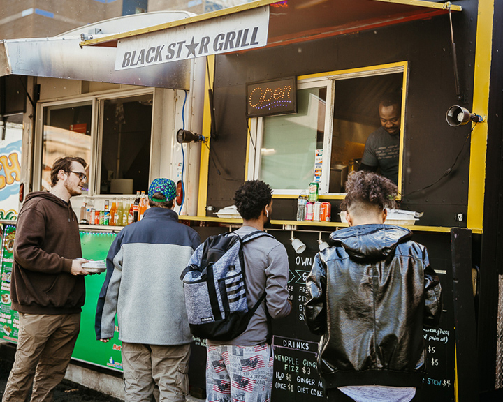 People lined up at a food cart serving African meals