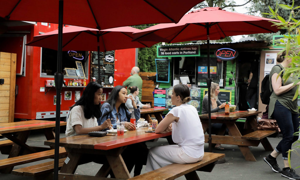 diners eating at a picnic table at an outdoor food cart pod