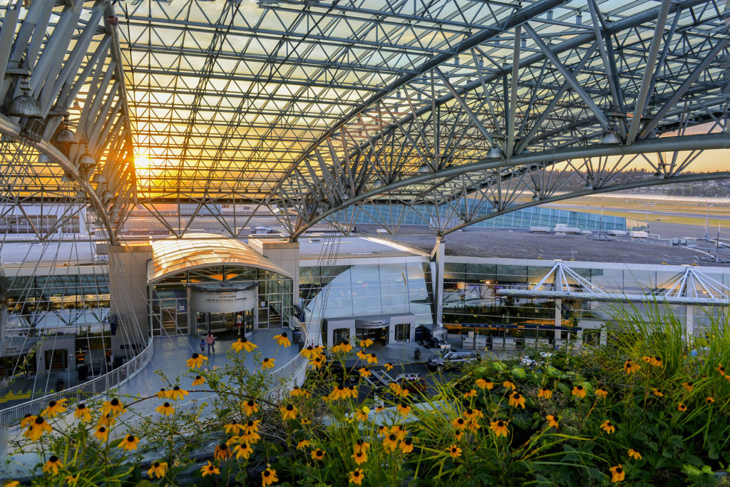 metal and glass canopy over Portland Airport entrances with flowers blooming in the foreground
