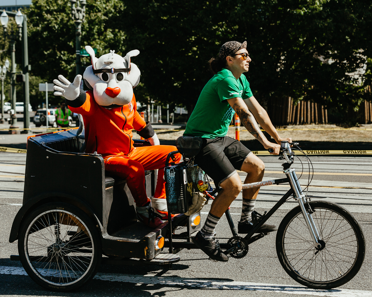 Blaze, the Trail Blazers mascot, rides by in a pedicab