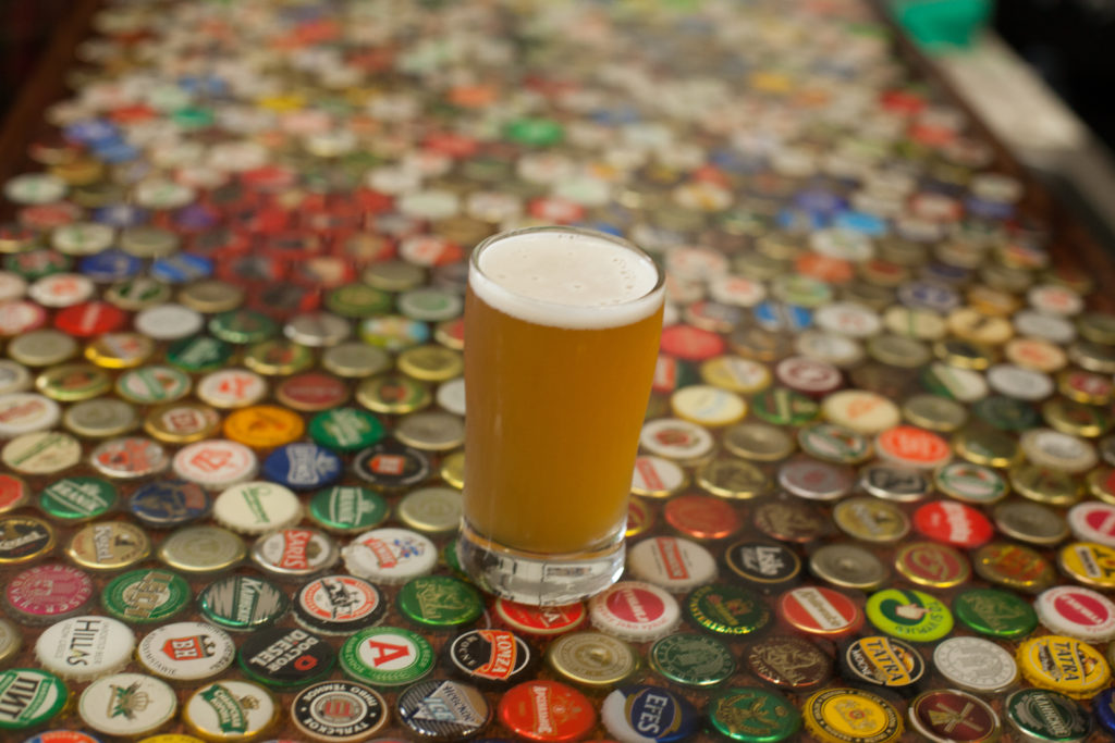 Pint of beer on bottlecap table