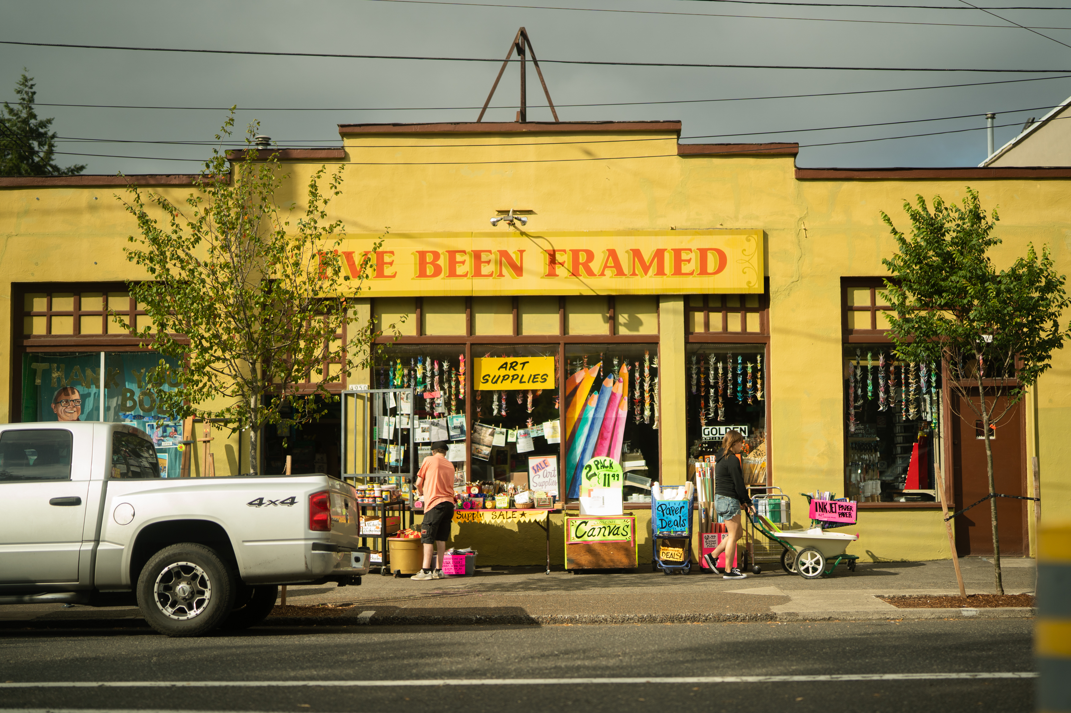 "Two people shop sidewalk offerings in front of a bright yellow storefront with a sign reading ""I've been framed"""