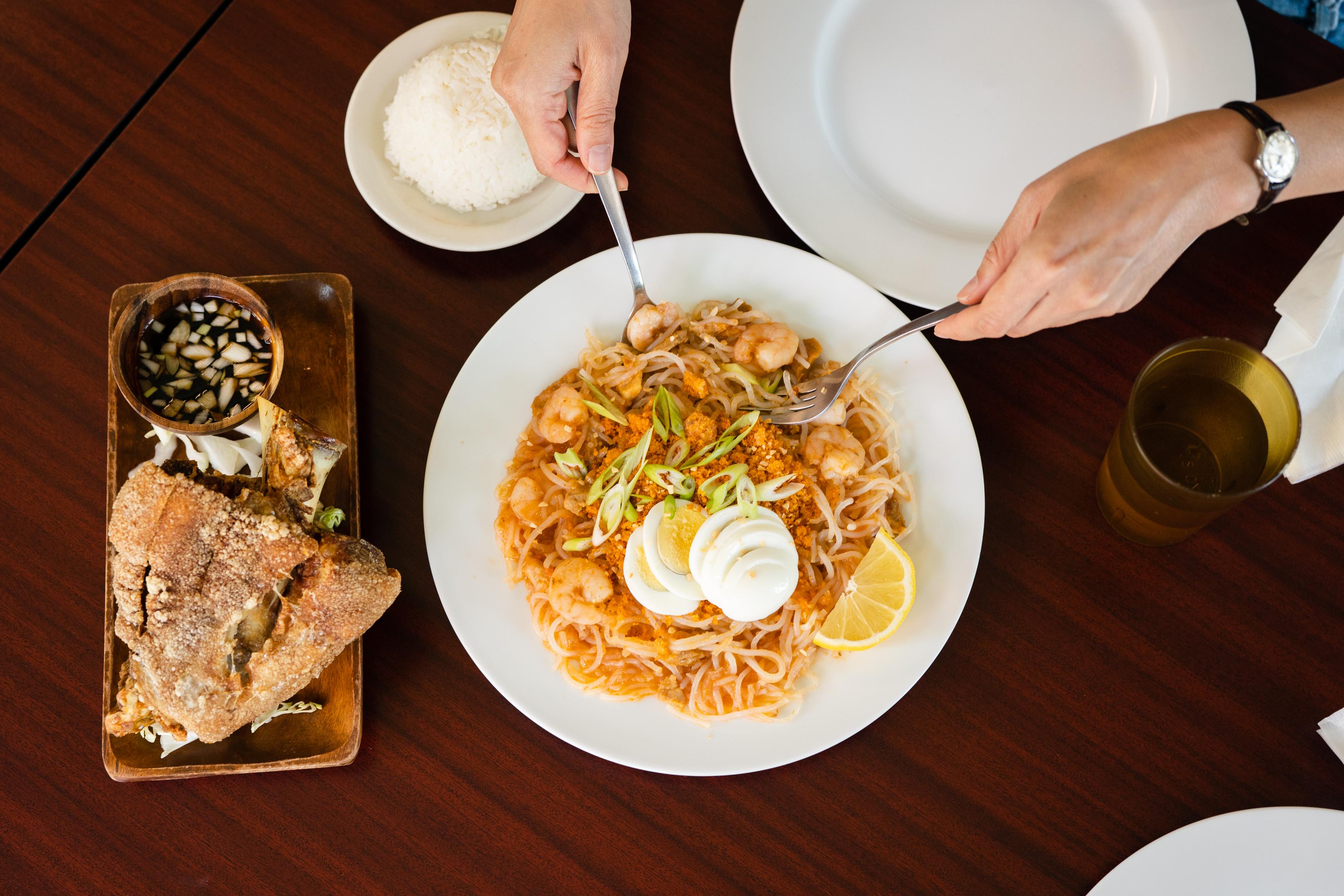 Two hands serve up a shrimp noodle dish, next to a crispy piece of pork