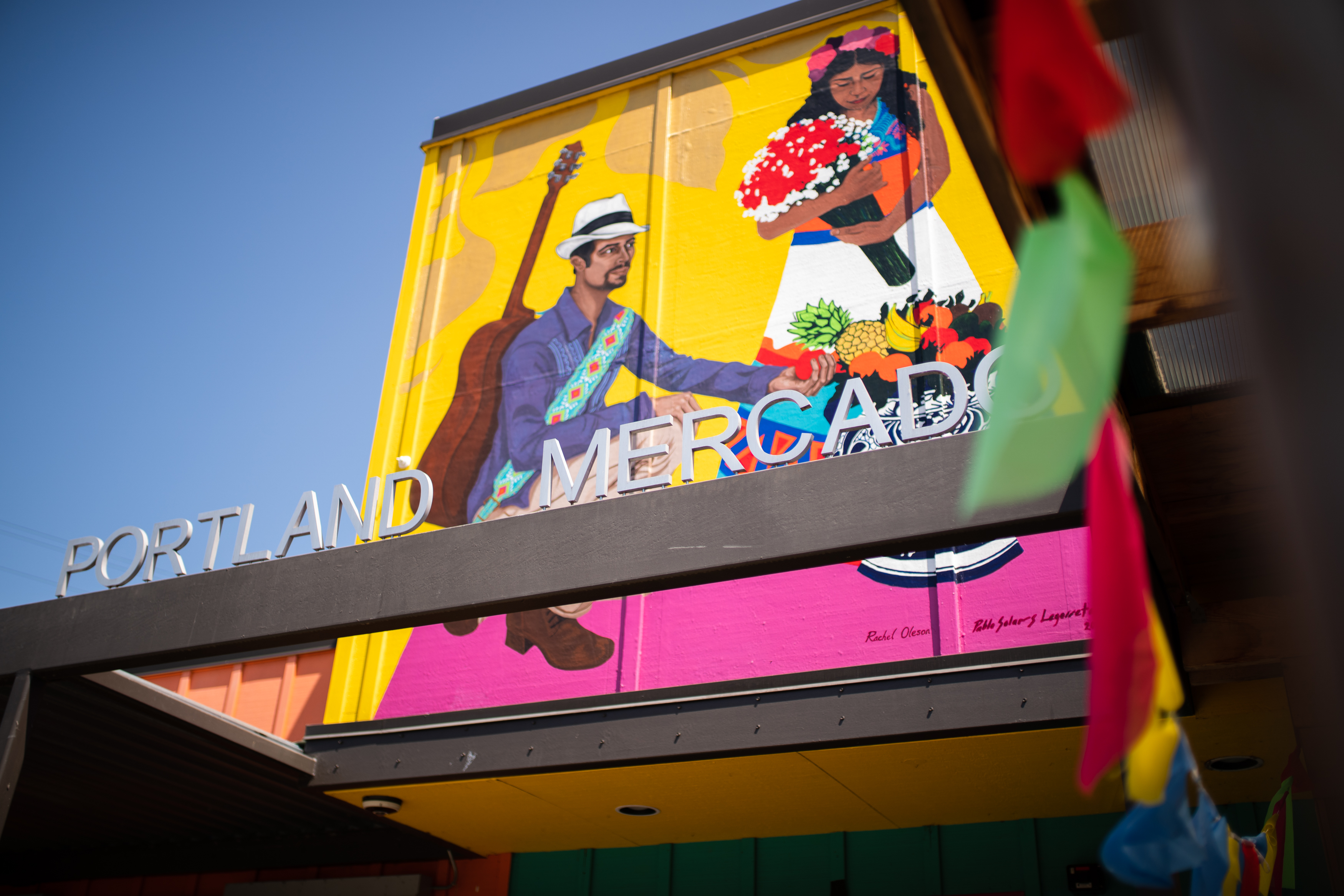 "A sign reading ""Portland Mercado"" in front of a brightly painted mural showing a Latin American dancer and musician"