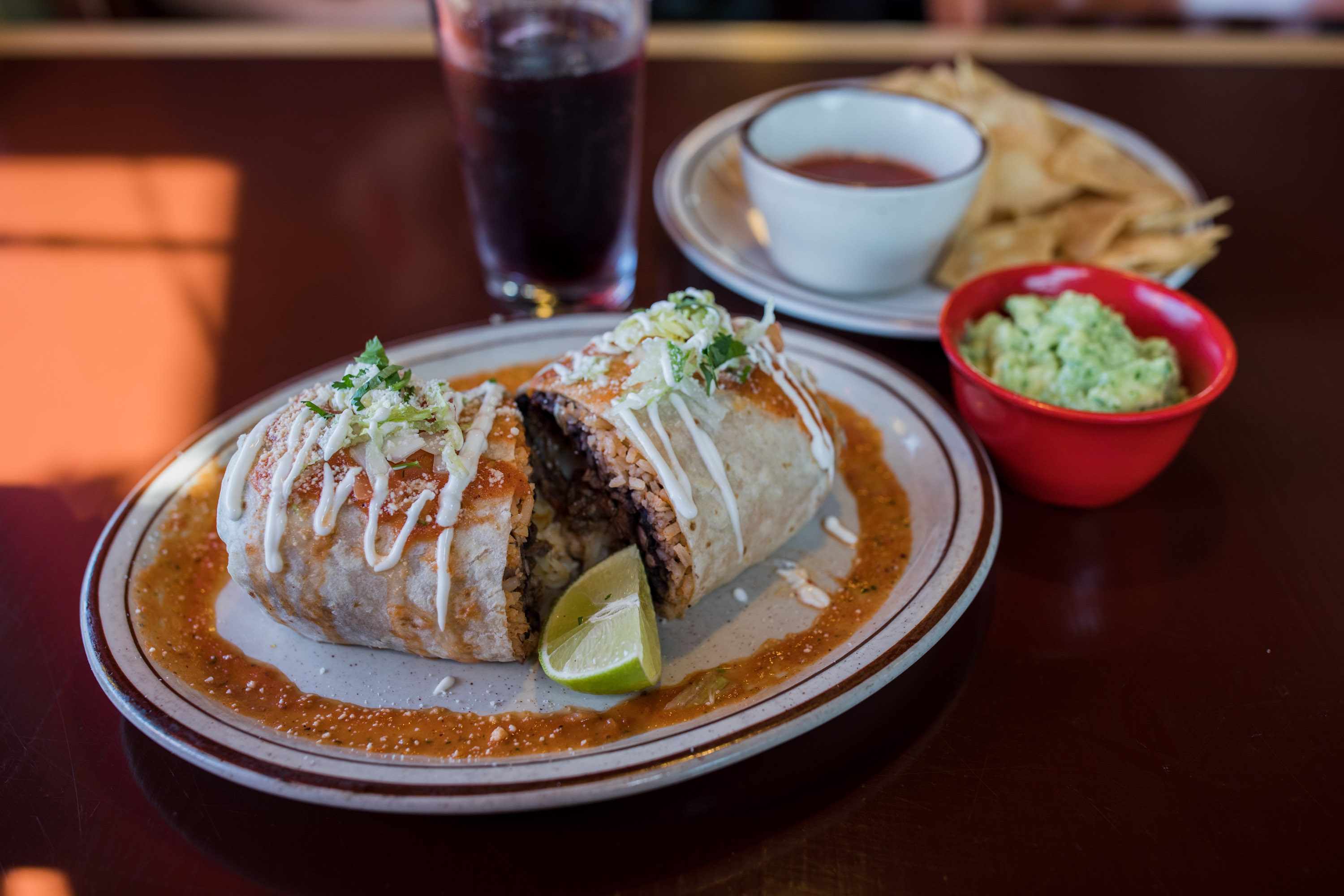 A burrito, sliced in half, on a plate with chips and salsa on the side
