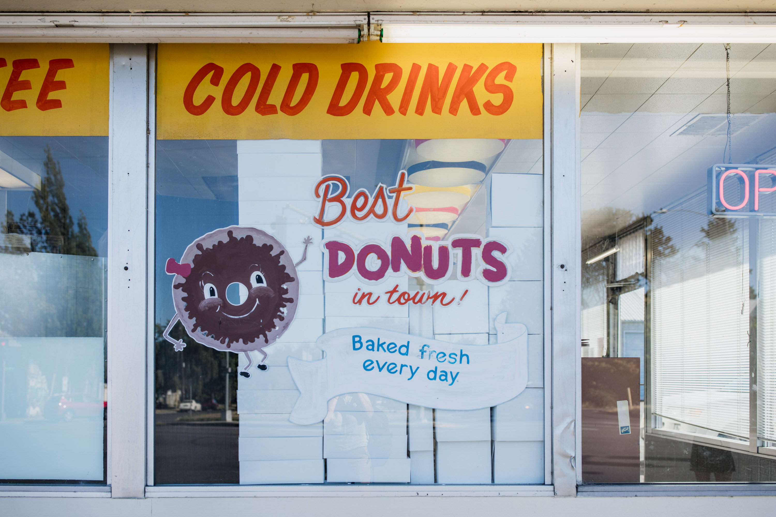 Painted window sign at a donut shop