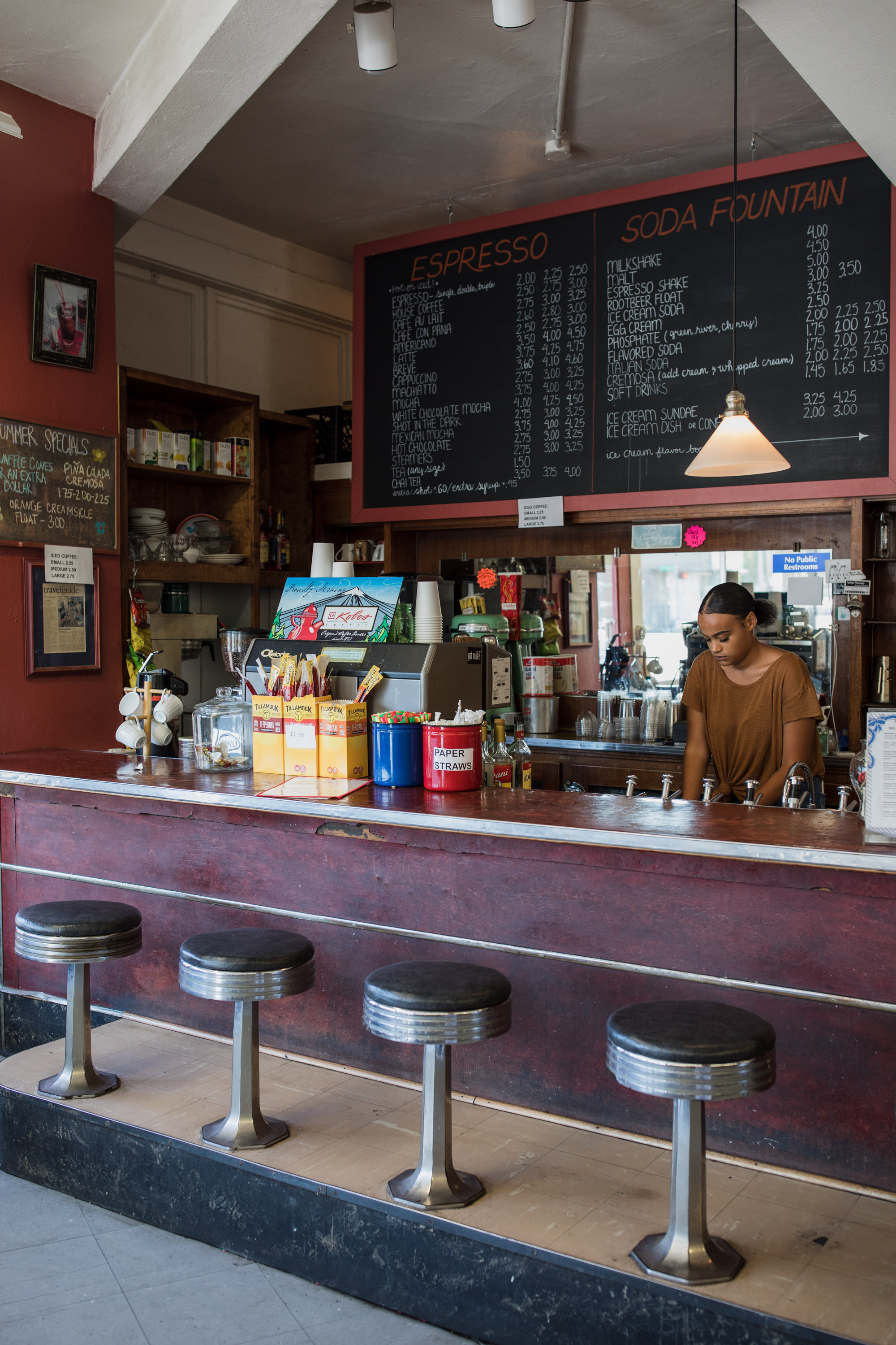 A woman works behind the counter of an old-fashioned soda fountain