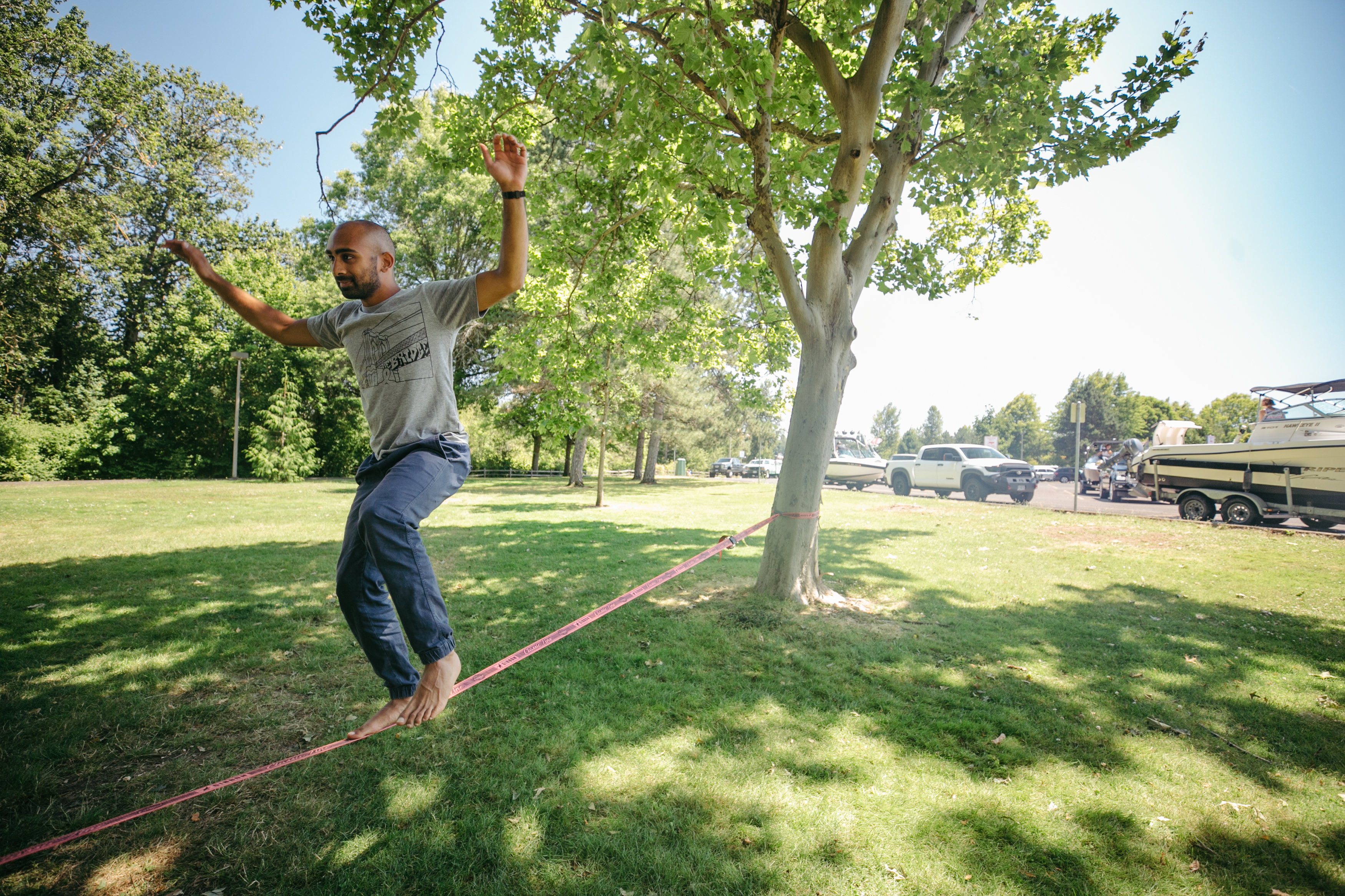A man balances on a slack line connected to a tree in a park