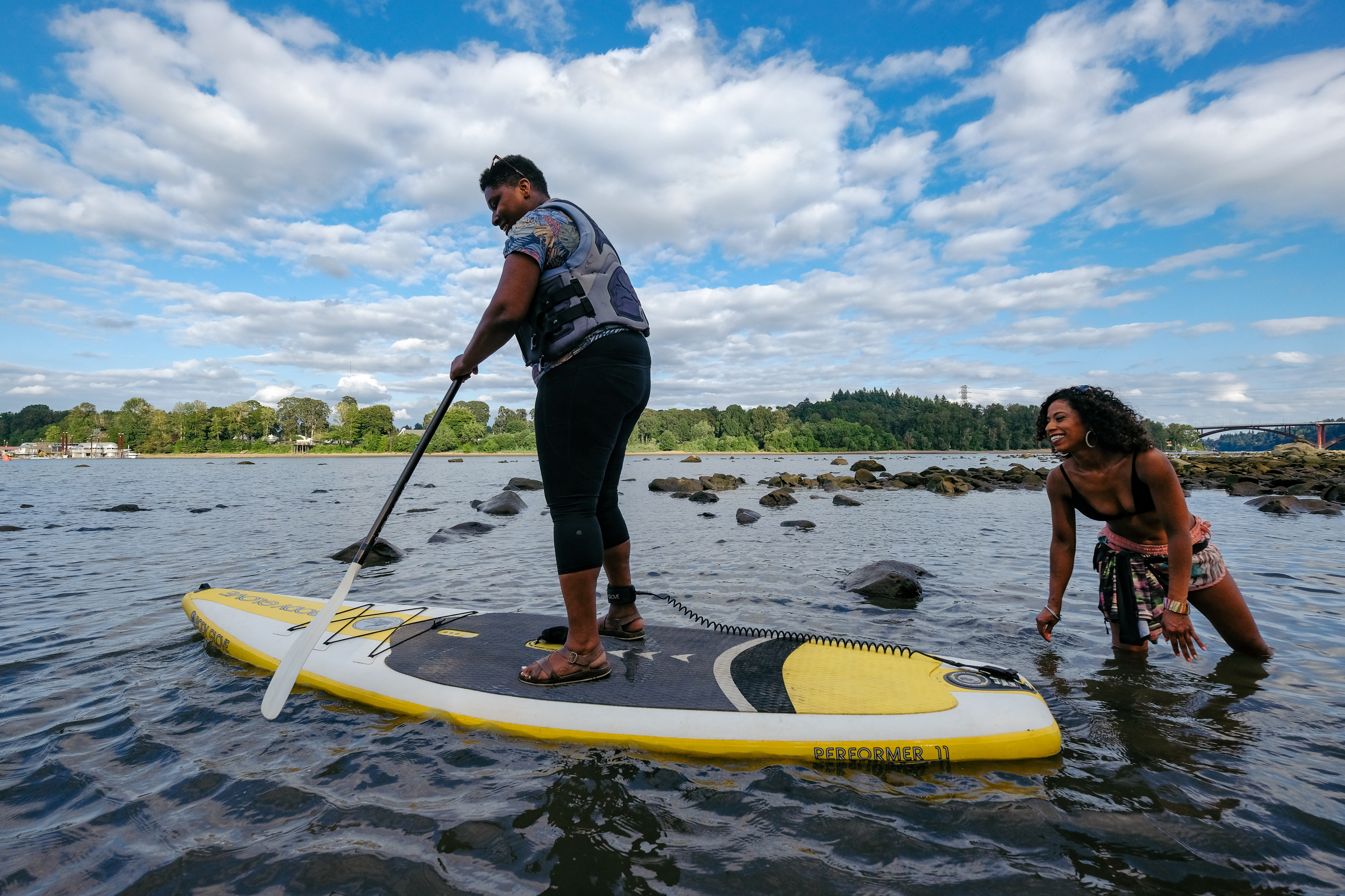 A woman pilots a stand-up paddleboard in a river, with another woman looking on